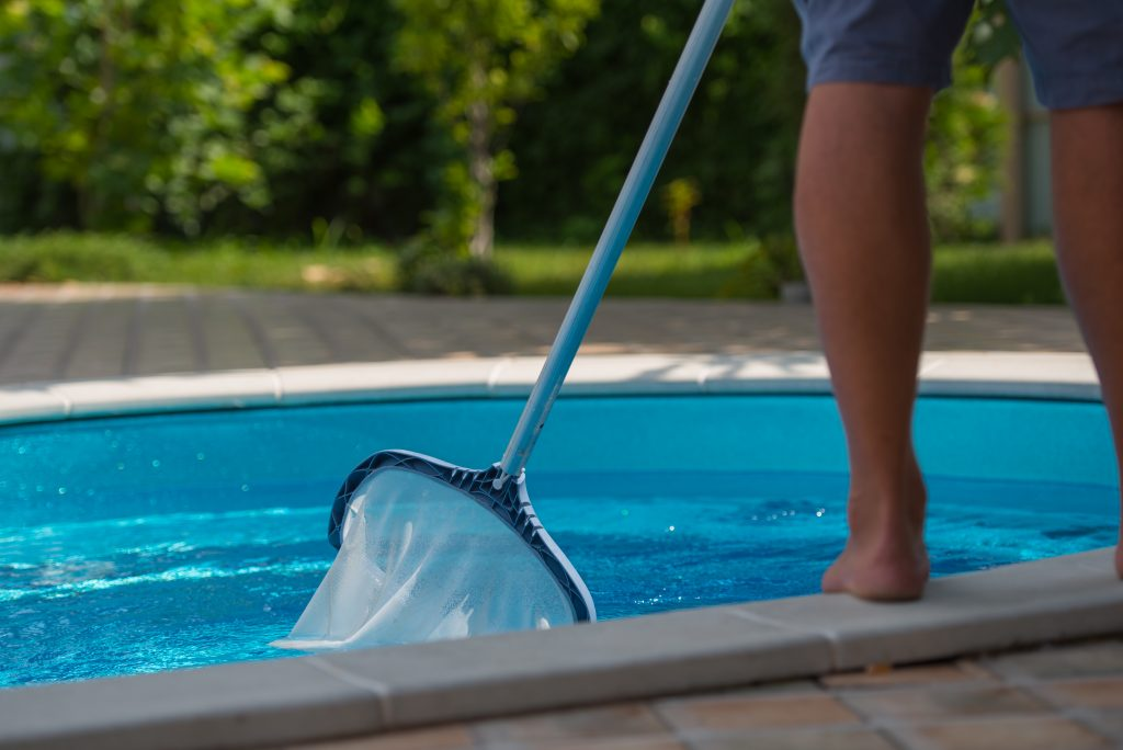 Man cleaning the swimming pool , net, closeup